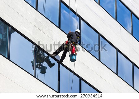 alpinist climber clean the windows of office building