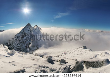 Alpinist climbing on Rysy mountain peak over clouds in High Tatras with clear blue sky and  on background - stock photo