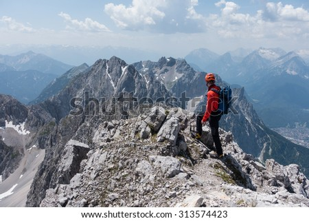 Alpinist enjoys the outlook to high mountain range.