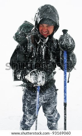 Alpinist facing a harsh blizzard - stock photo
