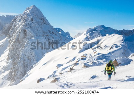 Alpinist hiking on the way to the peak. Photographed in the eastern Pyrenees, Catalonia, Spain. The peak is 2.930 meters high. The mountaineer is 20 years old. - stock photo