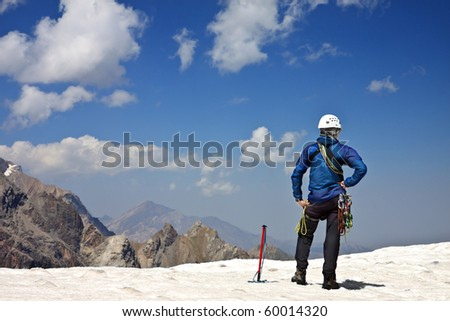 Alpinist with climbing equipment on the top of the snowy mountain - stock photo