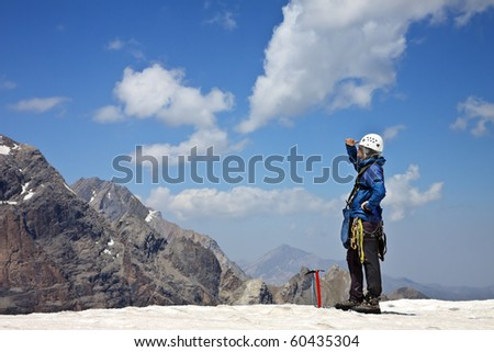 Alpinist with climbing equipment on the top of the snowy mountain looks into the distance - stock photo