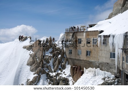 Alpinists arriving to the platform build on L'Aguille du Midi. The Aiguille du Midi (3,842 m) is a mountain in the Mont Blanc massif in the French Alps. - stock photo