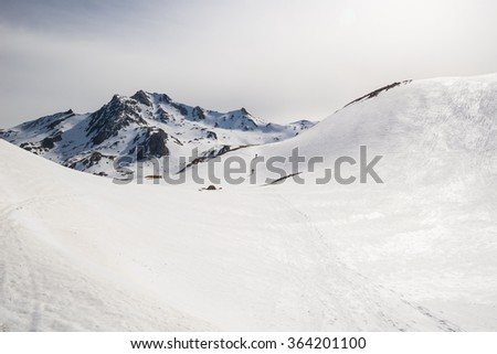 Alpinists hiking uphill by ski touring on snowy slope towards the mountain summit. Concept of conquering adversities and reaching the goal. Italian Alps. - stock photo