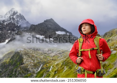 Alps Hiking - Asian hiker woman in Switzerland on trek in mountains with backpack living a healthy active lifestyle. Hiker girl on nature landscape hike in Urner Alps, Berne, Swiss alps, Switzerland. - stock photo