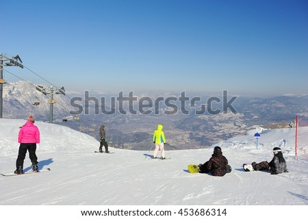 ALPS, ITALY - DECEMBER 17, 2015: There is a view to the Italian Alps. Snowboarders are coming down from the slope. On the right side there is the cable car. - stock photo