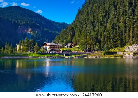 Alps mountain landscape. Lake and house on foreground. - stock photo