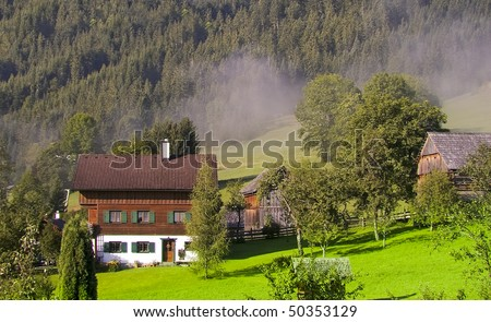 alps mountain valley gosau village in austria houses on green summer meadow and fog in morning light