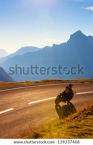 Alps mountains road with motorcyclist. - stock photo
