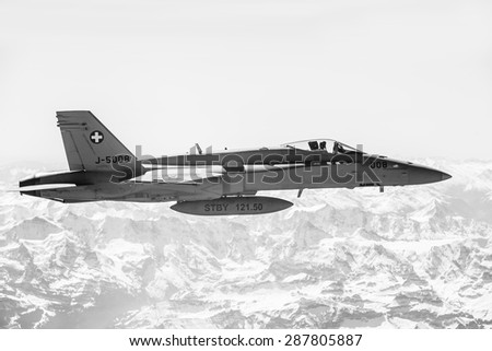 ALPS, SWITZERLAND - Apr 21, 2015: F-18 fighter jet of Swiss military air force on combat duty in the skies over Switzerland in the area of the Swiss Alps
