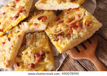 Alsatian onion pie with ham on wooden table closeup. Horizontal