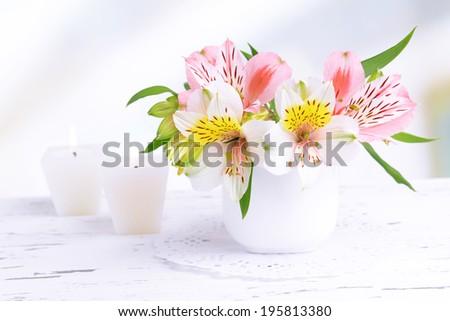 Alstroemeria flowers in vase on table on light background - stock photo
