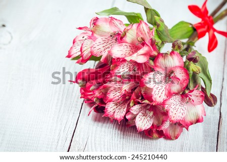 Alstroemeria flowers on wooden background. Peruvian lily or Lily of the Incas - stock photo