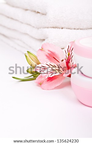 Alstroemeria pink flowers with moisturizing cream against stack of towels