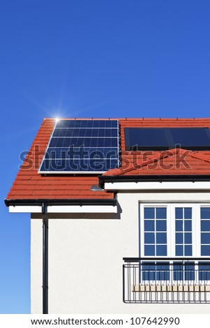 Alternative energy photovoltaic solar panels on tiled house roof - stock photo