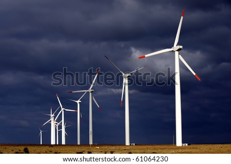 Alternative energy provided by windmills getting the most out of a stormy day - stock photo