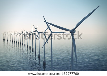 Alternative energy- shot of row of floating wind turbines during foggy morning. - stock photo