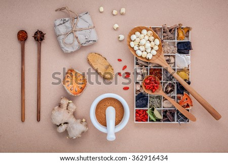 Alternative health care dried various Chinese herbs in wooden box , dried quince ,ginger and lotus seed in wooden spoon with mortar on brown background. - stock photo