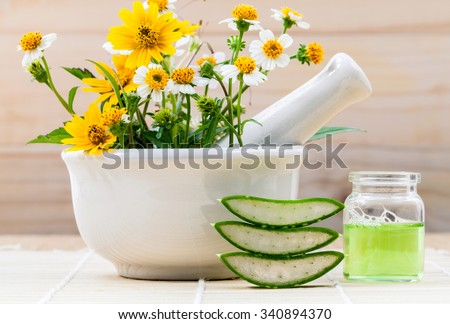 Alternative health care fresh herbal Aloe vera , oil and wild flower with mortar on wooden background. - stock photo