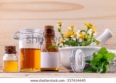Alternative health care fresh herbal ,honey and wild flower with mortar on wooden background. - stock photo