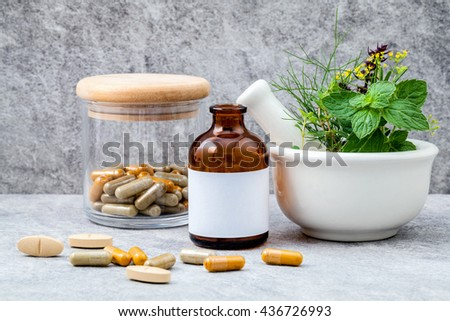 Alternative health care fresh herbs  rosemary ,lemon thyme ,fennel ,peppermint ,basil flower and herbal capsule with mortar on stone background.