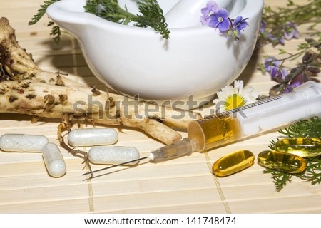 Alternative medicine and herbal extracts still life with a porcelain pestle and mortar with fresh medicinal herbs, flowers and roots with capsules and a syringe containing the extracts in front - stock photo