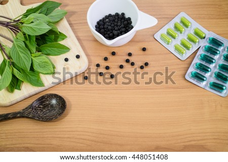Alternative medicine, blisters of capsules herbal pills, tablets on wood background. - stock photo