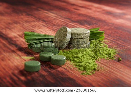 Alternative medicine, detox. Green superfood chlorella, wheat grass, barley grass and spirulina pills, powder and ground on wooden background. Healthy living, detoxify.  - stock photo