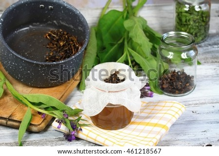 Alternative medicine, filtering comfrey ointment good for bones, decorated with fresh comfrey and dried comfrey roots