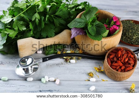 Alternative medicine herbs and stethoscope on wooden table background - stock photo