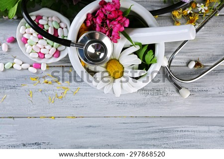Alternative medicine herbs, berries and stethoscope on wooden table background - stock photo