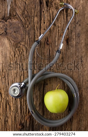 Alternative medicine - stethoscope and green apple on wood table top view . Medical background. Concept for diet, healthcare, nutrition or medical insurance - stock photo