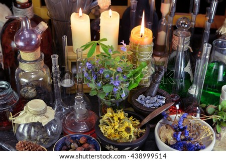Alternative medicine still life with bottles, flasks, candles, dry berries and herbs. Old pharmacy, esoteric or alchemic concept. Black magic and occult objects, medieval homeopathic still life - stock photo