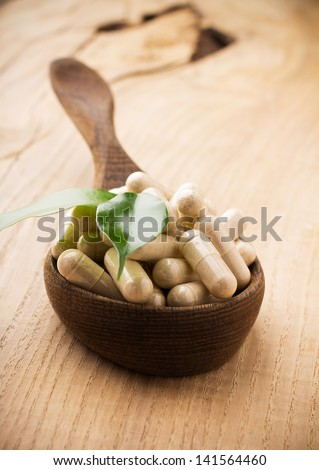 Alternative medicine tablets on a wooden spoon, green leaf. - stock photo