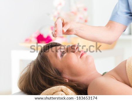 Alternative medicine, therapist using gemstones for lithotherapy - stock photo