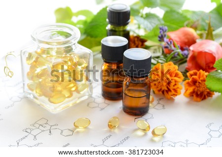 alternative medicine with supplements and essential oils on science sheet - stock photo