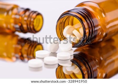 alternative medicine with white pills and brown medicine bottles - stock photo