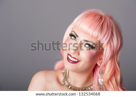 Alternative model with extreme makeup, artificial lashes and coral pink hair