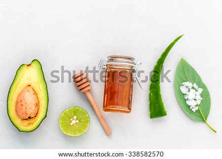 Alternative skin care  and scrub fresh  avocado , leaves ,sea salt , oils, lime and honey on marble background. - stock photo