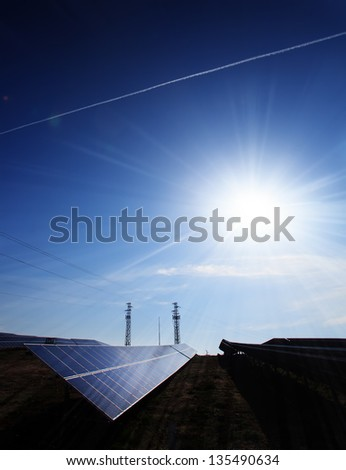 alternative solar electricity panels against the sun- vertical sun power image - stock photo