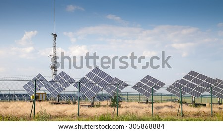 Alternative sources of producing electricity - PV meadow against the blue sky with white clouds - stock photo