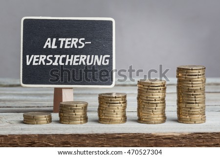 Altersversicherung (retirement insurance) in German language, white chalk type on black board, Euro money coin stacks of growth on wood table.