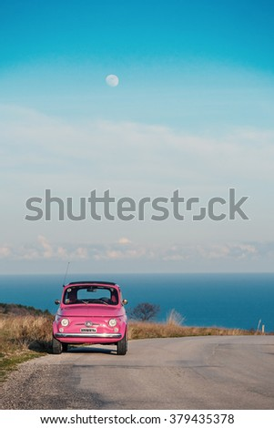 ALTIDONA, ITALY - FEBRUARY 20, 2016: Old pink Fiat Nuova 500 city car. Produced by the Italian manufacturer Fiat between 1957 and 1975. - stock photo