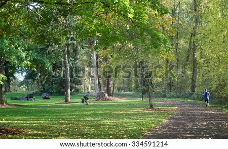 Alton Baker Park in Eugene Oregon provides a beautiful exercise environment for a lone jogger and bicycle rider. - stock photo