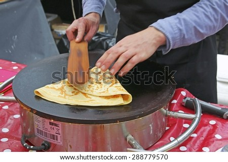 ALTRINCHAM, UK - JUNE 7 2015: A demonstration of the making of a lemon and sugar crepe at Altrincham market, Manchester. Altrincham is in Trafford, Greater Manchester and an affluent commuter town  - stock photo