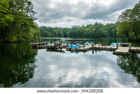 Aluminium bass fishing boat and pedalos at wooden dock in Virginia, America USA - stock photo