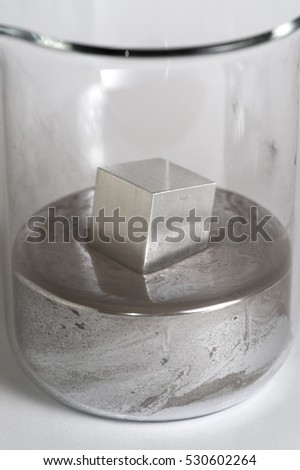 Aluminium cube floats in a beaker of mercury.