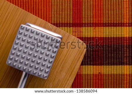 Aluminium meat tenderizer on wooden background. Kitchen equipment - stock photo