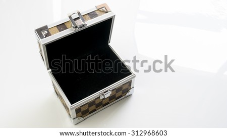 Aluminium metal checker box make up case or jewellery accessories box on empty background. Slightly de-focused and close-up shot. Copy space.